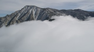 AX0010_093 - 5K stock footage aerial video tilt from snowy mountain to reveal tall peak in the San Jacinto Mountains in winter, California