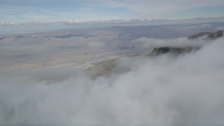 AX0010_094 - 5K stock footage aerial video of distant Little San Bernardino Mountains seen from layer of clouds, California