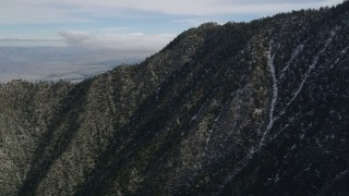 AX0010_102 - 5K stock footage aerial video fly over rugged slopes with patches of snow in the San Jacinto Mountains, California