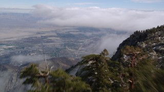 AX0010_105 - 5K stock footage aerial video fly over a rocky summit to reveal Cathedral City below wispy clouds, California