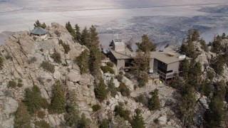 AX0010_106 - 5K stock footage aerial video orbit a rocky summit to reveal the Palm Springs Tramway in the San Jacinto Mountains, California