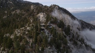 AX0010_108 - 5K stock footage aerial video orbit around a mountaintop tram station in the San Jacinto Mountains with light winter snow, California