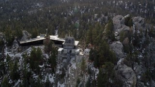 AX0010_109 - 5K stock footage aerial video of circling a mountain tram station in the San Jacinto Mountains with winter snow, California