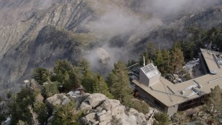 AX0010_110 - 5K stock footage aerial video orbit top of tram station in the San Jacinto Mountains with light winter snow, California
