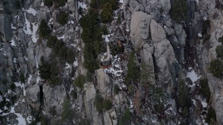AX0010_116 - 5K stock footage aerial video of tracking a gondola heading up a mountain with snow in the San Jacinto Mountains, California