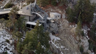 AX0010_117 - 5K stock footage aerial video orbit a gondola at a mountaintop tram station in the San Jacinto Mountains in winter, California