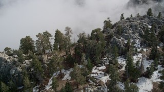 AX0010_118 - 5K stock footage aerial video pan across snow and boulders on a San Jacinto Mountains slope in winter, California