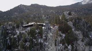 AX0010_119 - 5K stock footage aerial video of orbiting a mountaintop tram station in the San Jacinto Mountains with light snow, California