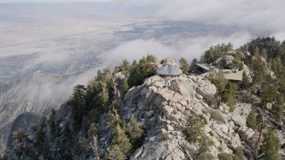 AX0010_121 - 5K stock footage aerial video tilt and fly over rugged mountain slope in the San Jacinto Mountains with light snow, California