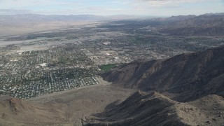 AX0010_127 - 5K stock footage aerial video fly over mountain ridge to reveal the North Palm Springs suburban neighborhoods, California