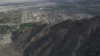 AX0010_129 - 5K stock footage aerial video orbit West Palm Springs suburban neighborhoods seen from the mountains, California