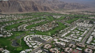 AX0010_131 - 5K stock footage aerial video fly over West Palm Springs neighborhoods and tilt to reveal golf course, California