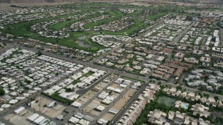 AX0010_131E - 5K stock footage aerial video fly over West Palm Springs neighborhoods and tilt to reveal and orbit golf course, California