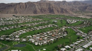AX0010_132 - 5K stock footage aerial video orbit homes and golf course in West Palm Springs, California