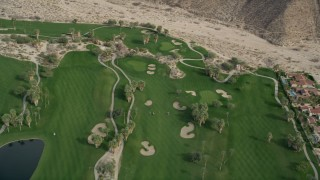 AX0010_134 - 5K stock footage aerial video fly over a road and golf course in West Palm Springs, California