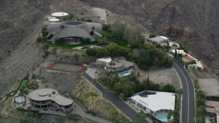 AX0010_136E - 5K stock footage aerial video orbiting a group of hilltop mansions in West Palm Springs, California