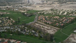 AX0010_140 - 5K stock footage aerial video orbit suburban neighborhoods and golf course in South Palm Springs, California