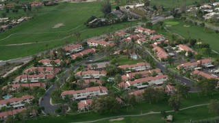 AX0010_141 - 5K stock footage aerial video orbiting apartment complex in South Palm Springs, California