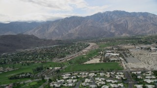 AX0010_142 - 5K stock footage aerial video of suburban neighborhoods in West Palm Springs near tall mountain range, California