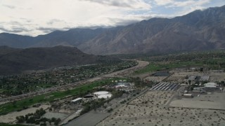 AX0010_143 - 5K stock footage aerial video orbit suburban neighborhoods near mountain range in West Palm Springs, California