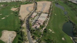 AX0010_148 - 5K stock footage aerial video tilt to bird's eye view of a mansion on a golf course in East Palm Springs, California