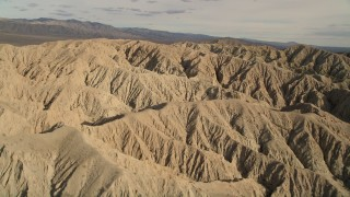 AX0011_005 - 5K stock footage aerial video fly over and orbit arid desert mountains in the Mojave Desert, California