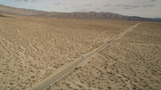 AX0011_006 - 5K stock footage aerial video orbit lonely desert highway in Joshua Tree National Park, California