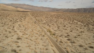 AX0011_007 - 5K stock footage aerial video approach and fly over a silver sedan on a lonely desert road in Joshua Tree National Park, California
