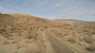AX0011_008E - 5K stock footage aerial video of following desert road through Joshua Tree National Park, California