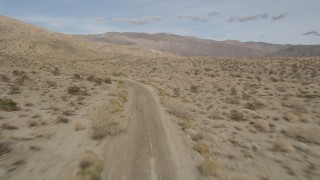 AX0011_009 - 5K stock footage aerial video of following a winding desert road in Joshua Tree National Park, California
