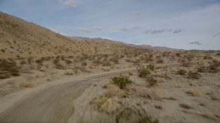 AX0011_010 - 5K stock footage aerial video fly low over a desert road and dry vegetation in Joshua Tree National Park, California