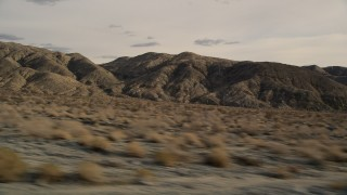 AX0011_014 - 5K stock footage aerial video fly low altitude by rugged desert mountains in Joshua Tree National Park, California