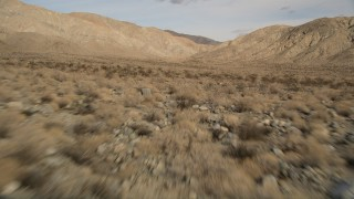 AX0011_015 - 5K stock footage aerial video of low altitude approach to desert mountains in Joshua Tree National Park, California