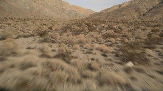 AX0011_017 - 5K stock footage aerial video tilt to reveal desert mountains in Joshua Tree National Park, California