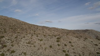 AX0011_023 - 5K stock footage aerial video fly low over desert mountain slope, Joshua Tree National Park, California