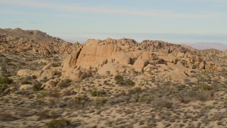 AX0011_038 - 5K stock footage aerial video fly by Joshua Trees and rock formations, Joshua Tree National Park, California