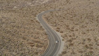AX0011_044 - 5K stock footage aerial video of tracking a white car traveling on a desert a road, Joshua Tree National Park, California