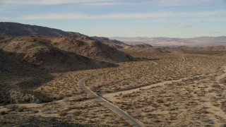 AX0011_045 - 5K stock footage aerial video of flying by a winding desert road, Joshua Tree National Park, California