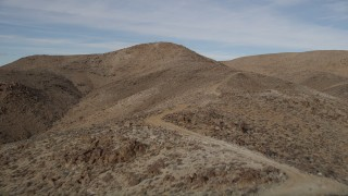 AX0011_053 - 5K stock footage aerial video of a mountain road in Mojave Desert, California
