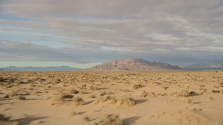 AX0012_001 - 5K stock footage aerial video fly low over desert toward mountains, Mojave Desert, California