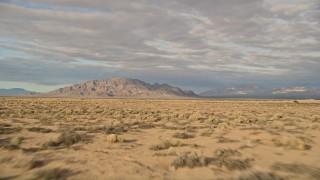 AX0012_003 - 5K stock footage aerial video fly over desert vegetation toward mountains, Mojave Desert, California