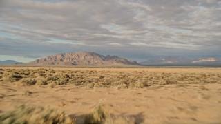 AX0012_004 - 5K stock footage aerial video fly over desert vegetation toward mountains, Mojave Desert, California