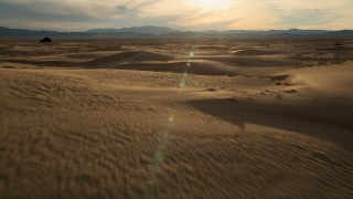 AX0012_037 - 5K stock footage aerial video of flying over sand dunes to open desert, Kelso Dunes, Mojave Desert, California