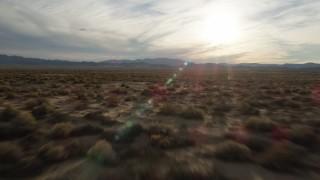 AX0012_039 - 5K stock footage aerial video fly low over desert plain toward the sun, Mojave Desert, California