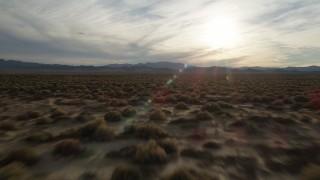 AX0012_040 - 5K stock footage aerial video fly low over desert plain toward the sun, Mojave Desert, California
