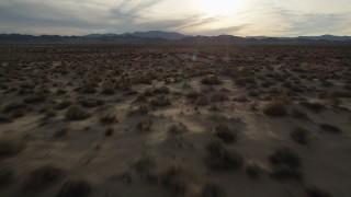 AX0012_042 - 5K stock footage aerial video fly low over desert plain, Mojave Desert, California, sunset