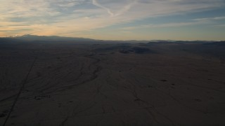 AX0012_055 - 5K stock footage aerial video of a flat desert plain at sunset in the Mojave Desert, California