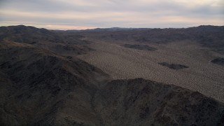 AX0012_059 - 5K stock footage aerial video fly by desert mountains, Mojave Desert, California, sunset