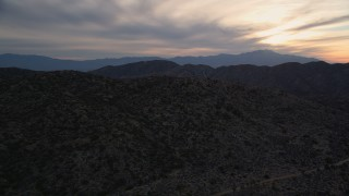 AX0012_060 - 5K stock footage aerial video fly over desert mountains, Mojave Desert, California, sunset