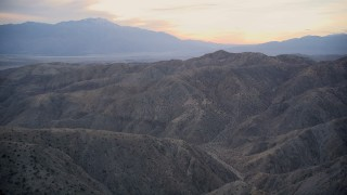 AX0012_063 - 5K stock footage aerial video fly over canyons and desert mountains, Mojave Desert, California, sunset